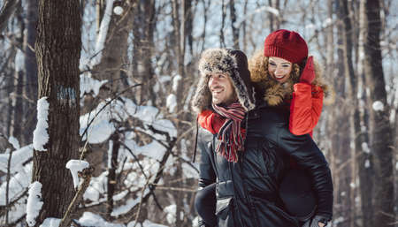 Man carrying his woman piggyback on a winter day in a joyful manner, they have fun in this season Stock Photo