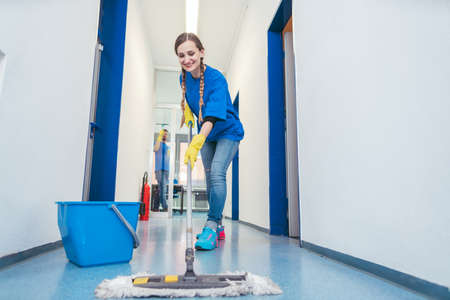 Cleaning lady mopping the floor in an office building, low shot Zdjęcie Seryjne