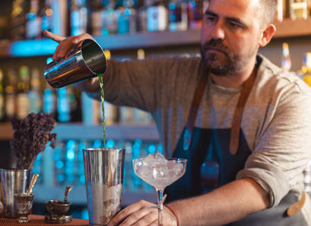 Barman gently pouring beer into shaker on bar counter