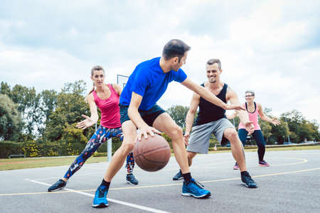 Basketball players playing at outdoors court Imagens