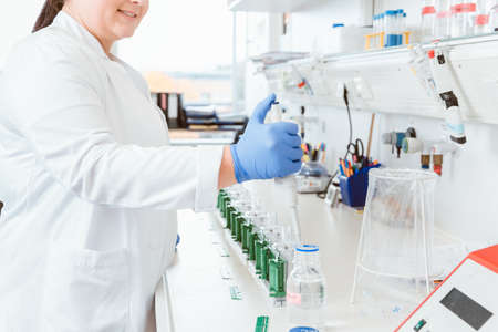 Woman doctor using dropper in lab