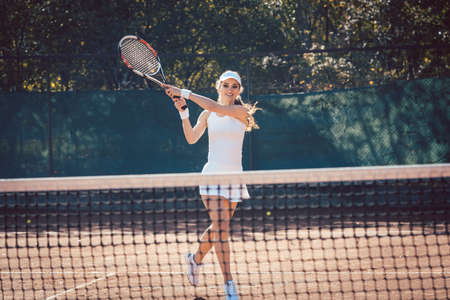 Woman forcefully playing tennis close to net 写真素材