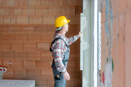 Senior male construction worker measuring the wall