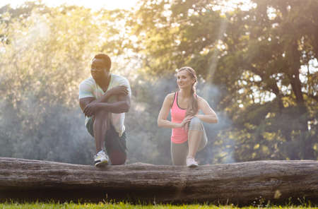 Black Caucasian couple stretching after exercise on tree trunk