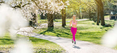 Fit woman running down a path during spring seen through blossom