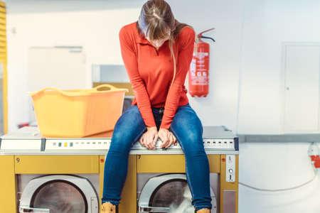 Woman sits on washing machine in laundromat