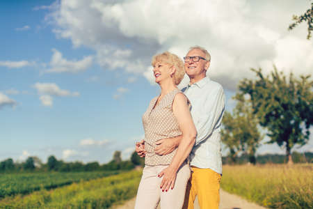 Senior couple in summer landscape looking into the future together