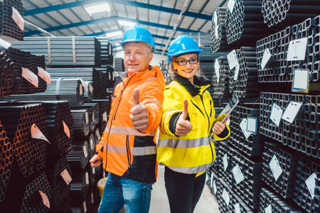 Worker team in warehouse of a steel trade showing thumbs up