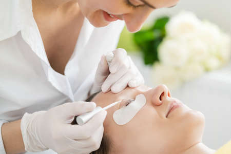 Cosmetician giving eyelash treatment to customer