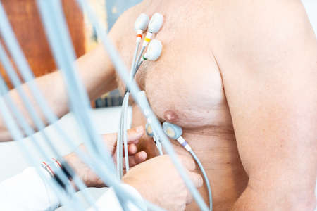Doctor placing electrodes on patient for ecg 写真素材
