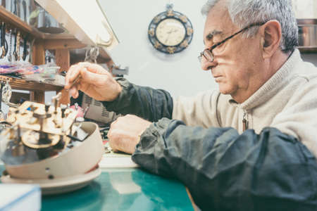 Watchmaker in his workshop repairing a larger clock