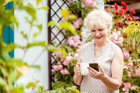 Senior lady or grandmother using phone to text her family
