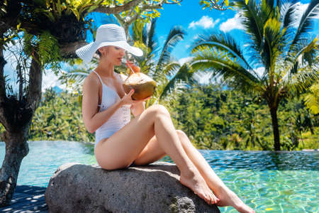 Woman with sunhat at the pool drinking a coconut