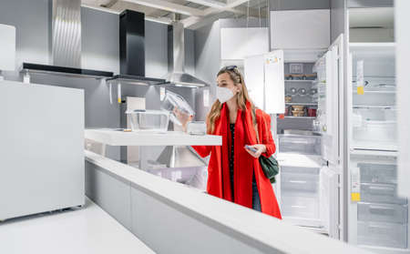 Woman with ffp2 mask shopping white goods in kitchen store 写真素材