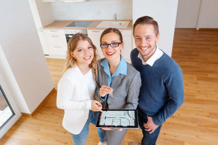House broker and clients in new apartment looking into camera
