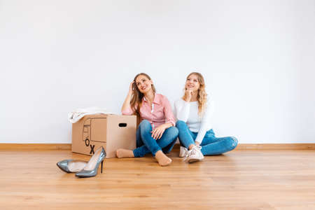 Two women in new apartment dreaming of how to decorate it