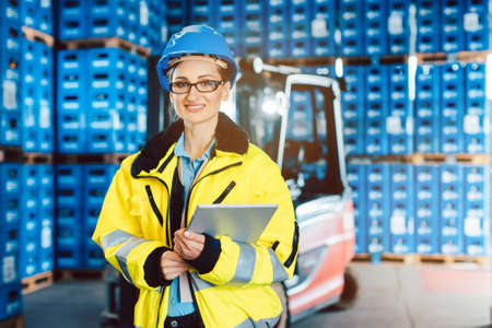 Worker woman in a logistics company with a tablet computer