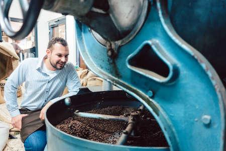 Man operating coffee roaster in factory 写真素材
