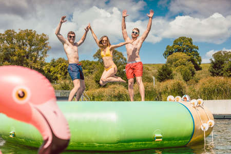 Friends having fun jumping off a tuby thingy thing in public pool