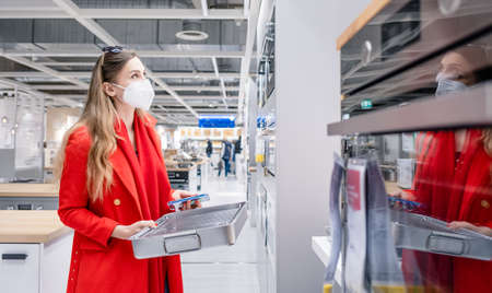 Woman looking for oven in kitchen store during pandemic with mask