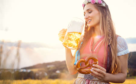Bavarian woman with beer and pretzel in beautiful landscape