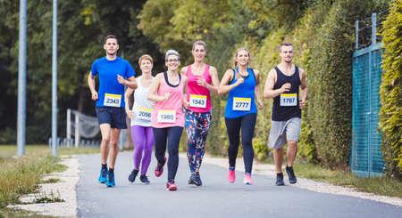 Group of marathon athletes running on street 写真素材