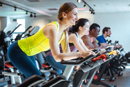 Caucasian woman and her friends on fitness bike in gym