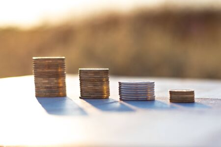 Stacks of coins laying down on the table on the beautiful sunset background, economy growth and strategy concept