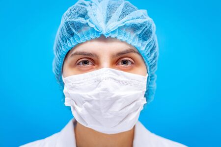 Young female doctor in medicine mask, hair cap and white gown portaiture on a blue background closeup shot. Shallow depth of field. Coronavirus, pandemia and medical care concept.