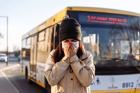 Young woman sneezes in a medical sterile mask on a bus station. Public transport issue during coronavirus outbreak. Stay home on quarantine. Epidemic, pandemia disease concept