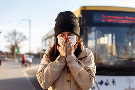 Girl in a brown coat coughs and sneezes on a bus station. Young woman wears medical sterile mask at a public transport. Coronavirus prevention. Covid-19