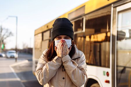 Young woman covers her face with hands while coughing and sneezing on a bus station and wearing white medical sterile mask. Girl using a public transport during coronavirus pandemia. Be aware