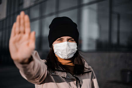 Young woman dramatic portrait showing stop sign with her hand against coronavirus. Say no to Covid-19 Chineese virus become a pandemia. Quarantine and isolation to prevent nCov2019