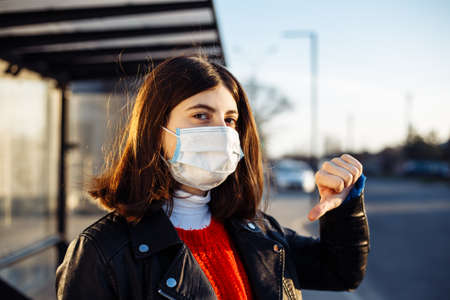 Girl shows thumb down and dislikes coronavirus worldwide pandemia. Young girl stands against using public transport during general epidemia of Chineese virus