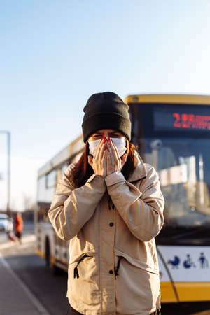 Young woman sneezes on a bus station and covers her face with hands. Girl wears a white medical mask standing near a bus at a public transport station. Coronavirus illness concept. Pandemia, epidemia Reklamní fotografie