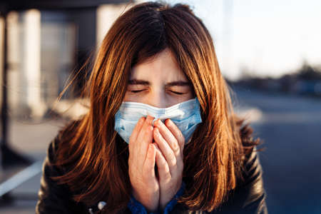 Young girl sneezes and coughs in a medical mask on a bus station. She feels fewer and headache because of a coronavirus symptoms. Stay home during quarantine and do not use public transport