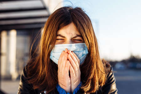 Young girl sneezes on a bus station and covers her face with hands. Girl wears a white medical mask standing near a bus at a public transport station. Coronavirus illness concept. Pandemia, epidemia