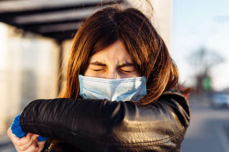 Young girl sneezes in a medical sterile mask on a bus station. Public transport issue during coronavirus outbreak. Stay home on quarantine. Epidemic, pandemia disease concept