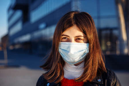 Portrait of a young girl in a medical sterile white mask staying safe from coronavirus. Prevent spread of covid-19 virus during quarantine. Girl looks forward to epidemic pandemia end