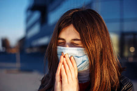 Young girl sneezes and coughs in a medical mask near a closed shoppong mall. She feels fewer and headache because of a coronavirus symptoms. Stay home during quarantine. Do not use public transport