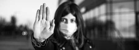 Wide angle closeup of young girl shows hand sign stop no to coronavirus epidemic pandemia originated at China. Covid-19 virus, nCov2019. Dramatic portrait of girl is against virus illness quarantine Reklamní fotografie