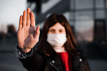 Young girl shows hand sign stop no to coronavirus epidemic pandemia originated at China. Covid-19 virus, nCov2019. Dramatic portrait of a girl is against virus and illness quarantine