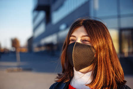 Portrait of a young girl in a black medical sterile mask staying safe from coronavirus. Prevent spread of covid-19 virus during quarantine. Girl looks forward to epidemic pandemia end