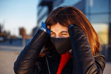 Close up of a young girl near closed mall struggles from a headache and hold her head with hands. Pain in a head because of coronavirus, flu symptoms, high temperature, fewer. Covid-19 virus concept Reklamní fotografie