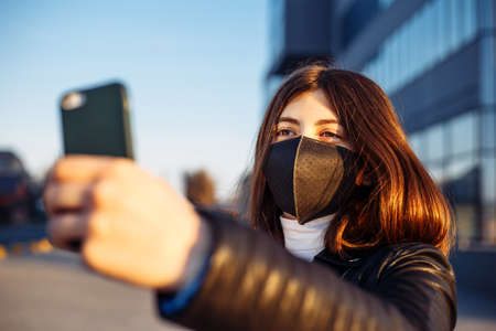 Young girl taking selfie photo in a black medical mask near a temporary closed shopping mall due to worldwide epidemic quarantine caused by Chineese coronavirus infection. Covid-19 nCov2019 concept