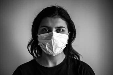 Monochrome portrait of a young woman wearing medical mask. Dramatic black and white closeup of a girl being protected from coronavirus and flu illness with sterile mask. Quarantine stay home concept