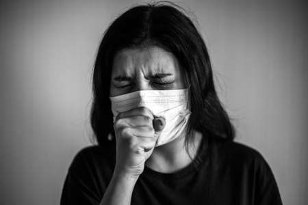Portrait of a young woman wearing medical sterile mask, coughs and covers with her hands. Dramatic black and white closeup of a girl being protected from coronavirus. Quarantine stay home concept