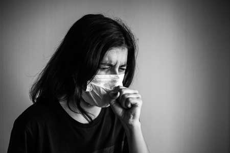 Portrait of a young woman wearing medical sterile mask, sneezing and covers with her hands. Dramatic black and white closeup of a girl being protected from coronavirus. Quarantine stay home concept Reklamní fotografie