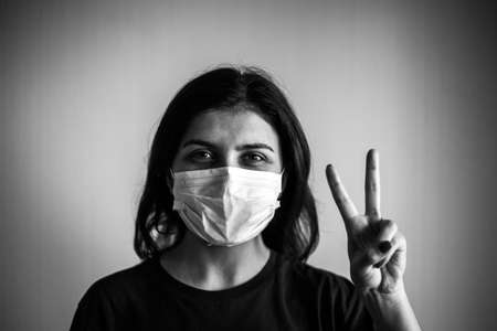 Portrait of a young woman wearing medical sterile mask, showing victory sign with her hand. Dramatic black and white closeup of a girl being protected from coronavirus. Quarantine stay home concept