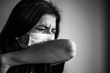 Portrait of a young woman wearing medical sterile mask, sneezing and covers with her elbow. Dramatic black and white closeup of a girl being protected from coronavirus. Quarantine stay home concept Reklamní fotografie
